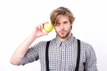 gatherer: Idea of proper nutrition. Healthy lifestyle and diet concept. Man with serious face, beard and stylish hairdo holds apple near ear. Macho with fresh fruit and suspenders, isolated on white background Stock Photo