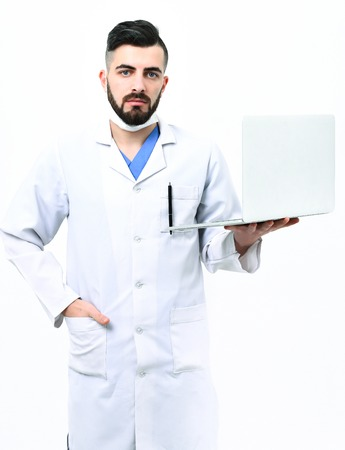 Physician in surgical mask isolated on white background. Man with satisfied and serious face in white hospital uniform. Treatment and medical technologies concept. Doctor with beard holds white laptop Stock Photo