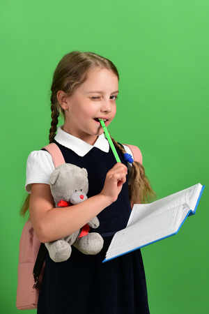 Back to school and education concept. Girl holds teddy bear, open notebook and green marker. School girl with flirty smile isolated on green background. Pupil in school uniform with braids and bag Stock Photo
