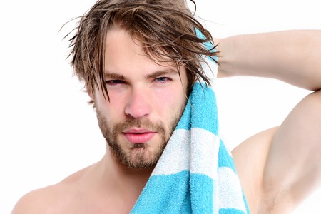 Strength and sportive shape idea. Macho with striped towel and big muscles isolated on white background. Bearded man with naked body and confident face wipes his hair. Shower time and sports concept Standard-Bild