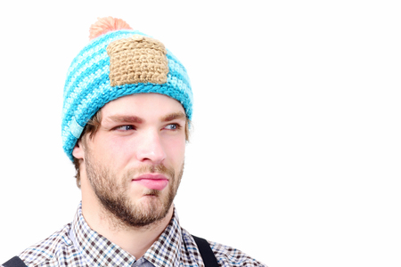 Man in winter hat and plaid shirt isolated on white background. Bearded man with suspicious face wears hat. Guy with stylish hat in blue beige and orange color. Winter and casual style clothes concept Stock Photo