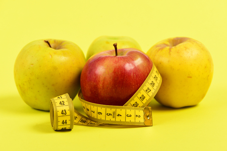 Apples and ruler. Fresh juicy fruit in yellow and red colour belted with twisted yellow measuring tape, isolated on bright yellow background, defocused. Concept of diet and slim shape