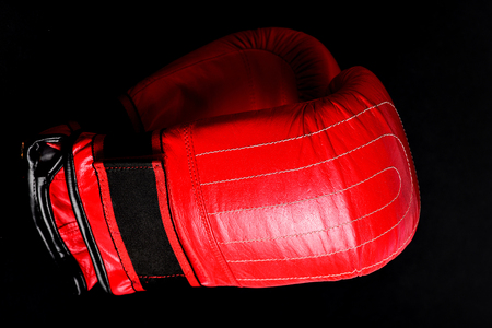 Duet of gloves for boxing made of red leather isolated on black background, close up. Concept of individual sports and heavyweights