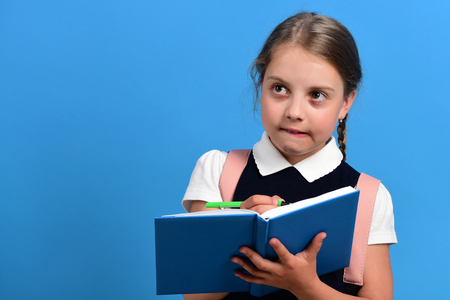 Pupil in school uniform with braid. Girl writes in big blue notebook. School girl with thoughtful face on blue background, copy space. Back to school and education concept 写真素材