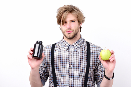 Macho with fresh fruit and bottle of pills, isolated on white background. Health and diet concept. Man with suspicious look and serious face, beard and stylish hairdo holds green apple and drugs
