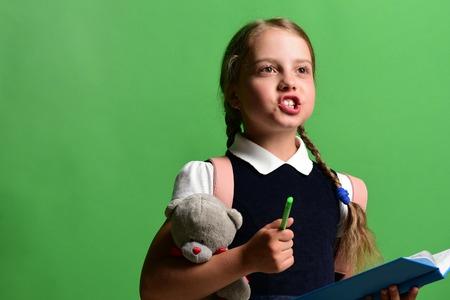 Pupila en uniforme escolar con trenzas y mochila rosa. Volver a la escuela y el concepto de educación. La muchacha de la escuela dice algo, aislada en fondo verde. La muchacha sostiene el oso del juguete, abre el libro azul y el marcador Foto de archivo - 82696662