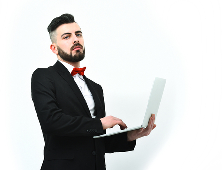 hair stylist: Businessman or insurance agent with beard and moustache, attentive look and serious face works on his laptop, isolated on white background, copy space. Concept of high technology and working online Stock Photo