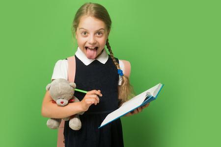 Tude et retour au concept de l'école. L'élève tient le livre bleu, le marqueur et l'ours en peluche. Kid en uniforme scolaire, isolé sur fond vert avec espace copie. Fille avec des tresses met sa langue Banque d'images - 82696832