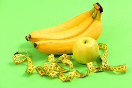 Apple in green color, bananas and yellow tape for measuring untwisted curly, isolated on light green background. Concept of diet and healthy food