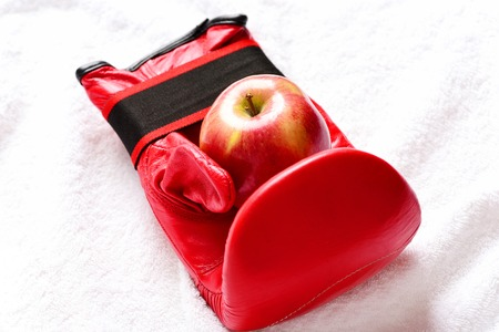 Sport equipment and fruit on white towel background, close up. Professional box fight and dieting concept. Boxing gloves in red color. Pair of leather boxing sportswear with juicy red apple Stock Photo