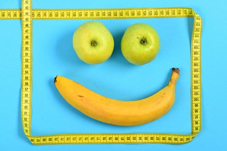 smiley pouce: Smile made of banana and green apples framed with yellow flexible ruler isolated on cyan blue background. Concept of happiness and food art Banque d'images