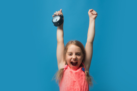 Pupil with braids, isolated on blue background. Back to school and childhood concept. Girl with black alarm clock. Kid screams with happy face and hands up. Stock Photo