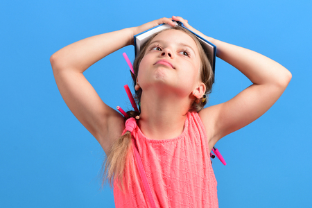 Kid in pink dress with braids and pencils in hair. School girl with dreaming face isolated on blue background. Girl holds her head up with open notebook on it. Back to school and education concept