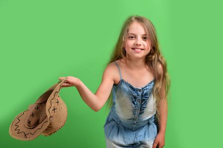 Meisje in mooie outfit houdt cowboyhoed. Kind met een blij gezicht en lang blond haar draagt ??een spijkerjurk. Mode en casual stijl concept. Dame in stijlvolle kleding geïsoleerd op groene achtergrond