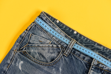Close up of jeans belt loops and pocket. Healthy lifestyle and dieting concept. Top part of denim trousers isolated on yellow background. Jeans with blue measure tape instead of belt. Stock Photo