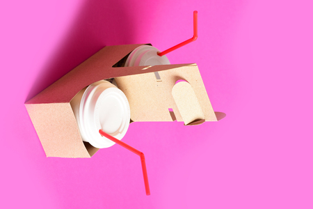 Set of disposable cups with covers and red straws placed in cardboard holder on light pink background. Concept of takeaway food Stock Photo