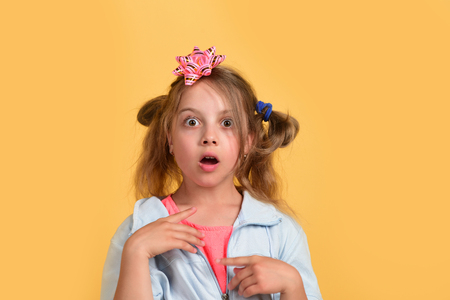 School girl and paper bow for present boxes. Girl with surprised or shocked face isolated on warm yellow background. Kid with cute pink bow on head and messy hair. Holiday and present concept. Reklamní fotografie