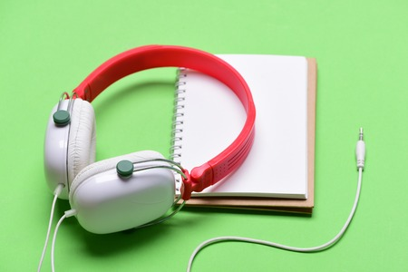 Headphones in white and red color with empty notebook. Music accessories and note taking concept. Modern and stylish earphones isolated on light green background. Headset for music and blank page 版權商用圖片