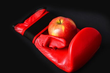 Professional box fight and dieting concept. Pair of leather boxing sportswear with juicy red apple. Boxing gloves in red color. Sport equipment and fruit on black background Stock Photo