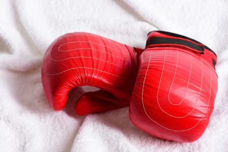 Concept of martial arts with pair of red gloves for thai boxing and white towel background Stock Photo