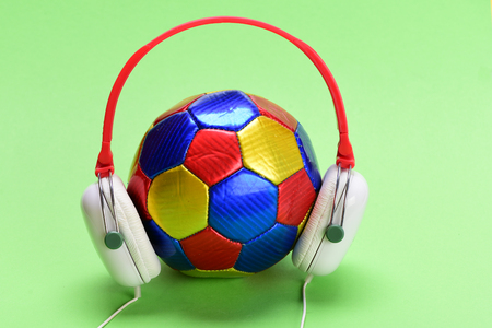 Headphones in white and red color with colorful soccer ball. Modern earphones and football isolated on light green background. Headset for music placed on ball. Music and sports equipment concept