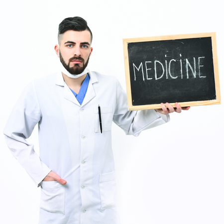 barbershop: Doctor with beard holds little blackboard with word medicine written on it. Man with serious face in white medical gown isolated on white background. Treatment, recovery and ambulance services concept