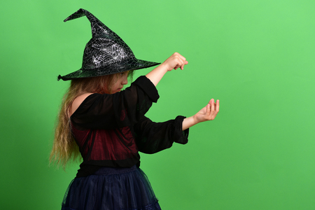 Kid in black witch hat, dress and serious face. Magician in witch costume. Girl tries to put spell on something, isolated on green background, copy space. Halloween and autumn holiday concept