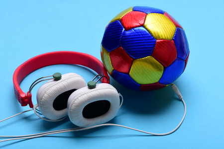 Modern earphones and football on turquoise background. Headphones in white and red color with colorful soccer ball. Music and sports equipment concept. Headset for music placed on ball Stock Photo