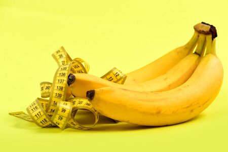 Fruit and measuring tape composition, isolated on light yellow background, symbol of diet and vitamins