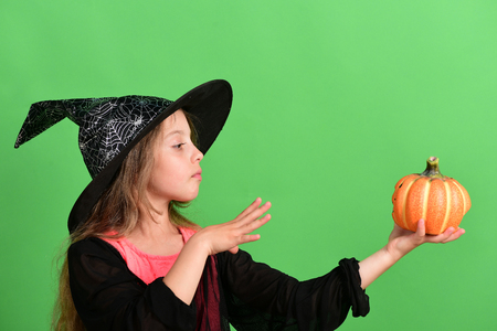 Kid in black witch hat, dress and concentrated face. Girl with carved orange pumpkin isolated on green background. Halloween and autumn concept. Child in witch costume puts spell on jackolantern