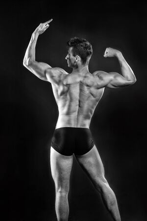 Man with muscular body. Adam with bare back. Sport and workout. Athletic bodybuilder pose in pants. Gladiator or atlant, black and white