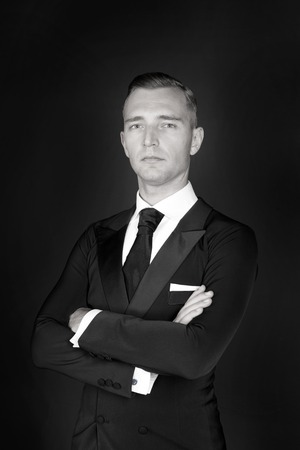 ceo: business Man in a black tuxedo suit and white shirt and black tie on a black background. Without a face. The businessman in the dark. Studio shot