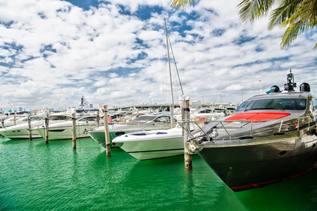 docked: luxury yachts docked in the port in bay at sunny day with clouds on blue sky in Miami Stock Photo