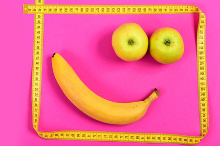 smiley pouce: Happiness concept with apple and banana face and frame of measuring tape in yellow color isolated on pink background