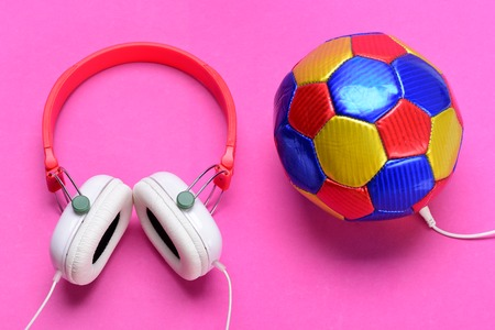 Headset for music near soccer ball as player. Music and sports equipment concept. Modern earphones and football isolated on pink background, top view. Headphones in white and red with colorful ball Stock Photo