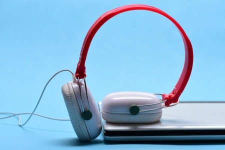 Sound recording idea. Music and digital equipment concept. Electronics isolated on light blue background. Headphones and silver laptop. Earphones in red and white colors made of plastic with computer. Stock Photo