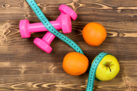 orange, apple with measuring tape and weight dumbbells for diet concept on brown vintage wooden background Stock Photo