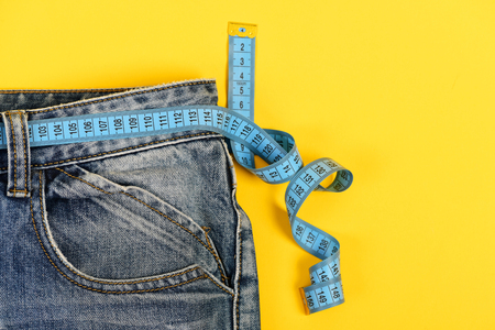 Healthy lifestyle and dieting concept. Blue jeans with measure tape instead of belt. Close up of jeans with measure tape around waist. Upper part of denim trousers isolated on yellow background.