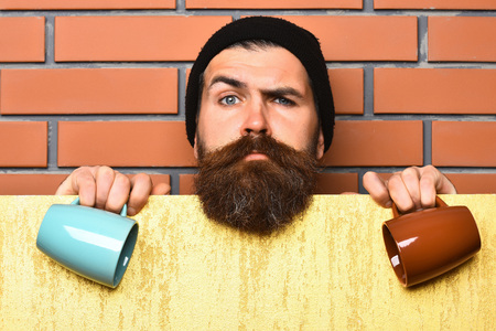 barbershop: Bearded man, long beard. Brutal caucasian serious unshaven hipster in black hat with yellow paper sheet holding colorful cups on brown brick wall studio background