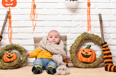leaned: small baby boy with adorable curious face in yellow sweater leaned on pillow in knitted scarf around halloween decorations on white brick wall background Stock Photo