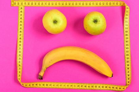 smiley pouce: Pommes et bananes encadrées de ruban à mesurer jaune faisant face triste et déçu, isolé sur fond rose vif. Concept d'expression de visage