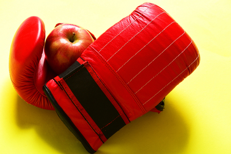 Pair of leather boxing sportswear with juicy red apple. Knock out and healthy nutrition concept. Sport equipment and fruit on light yellow background. Boxing gloves in red color