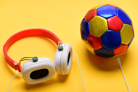 Headphones in white and red color with colorful soccer ball. Headset for music placed near ball. Music and sports equipment concept. Modern earphones and football on warm yellow background