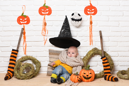 leaned: small baby boy with adorable curious face in yellow sweater leaned on pillow in knitted scarf and black witch hat around halloween decorations on white brick wall background Stock Photo