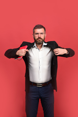 Businessman with strict face and glasses on light red background. Guy with closed red notebook. Success, business and studying concept. Man in classic outfit with beard holds red book or organizer