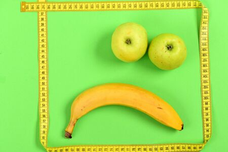 smiley pouce: Tape for measurement making frame with banana and apple inside: sad face isolated on green background. Disappointed smiley expression