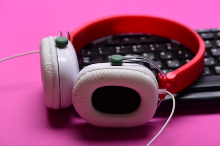 Headphones and black keyboard. Music and call center concept. Sound recording and technology idea. Electronic appliances on pink background. Earphones in red and white colors with computer keyboard
