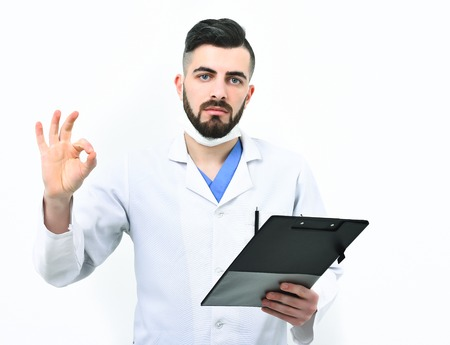 barbershop: Guy in surgical mask isolated on white background. Treatment and ambulance service concept. Man with serious face in white coat. Doctor with beard holds clip folder for prescriptions and shows ok sign