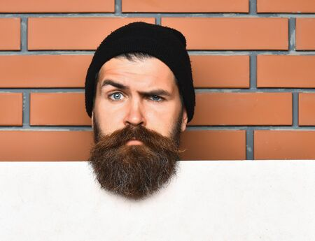 barbershop: Bearded man, long beard. Brutal caucasian serious unshaven hipster in black hat with white paper sheet on brown brick wall studio background, copy space