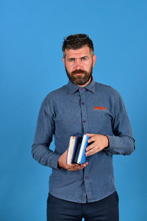 barbershop: Textbooks in blue color in guys hands on blue background. Teacher wears glasses and holds notebooks. Professor with serious face expression. Knowledge and studying concept. Man with beard and books